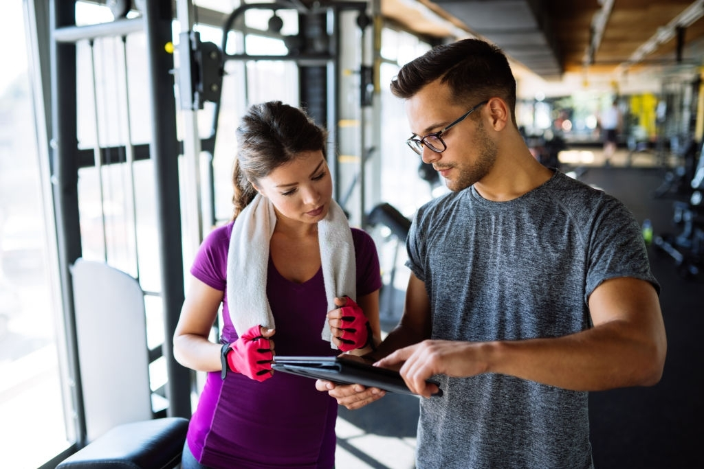 Woman and personal trainer making exercise plan in gym